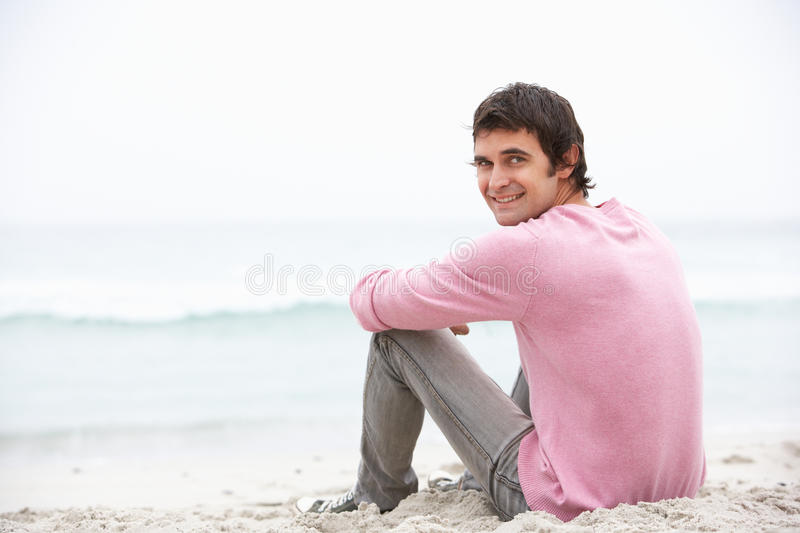 Download Young Man On Holiday Sitting On Winter Beach Stock Photo - Image: 15250032