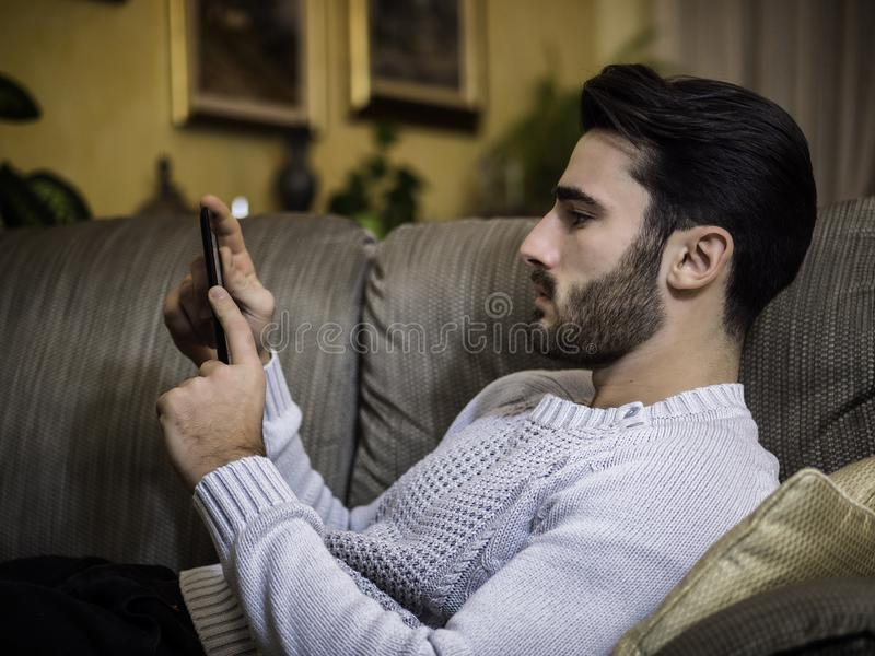 Young man at home reading with ebook reader. Handsome young man at home, reading with ebook reader lying on a couch stock photo