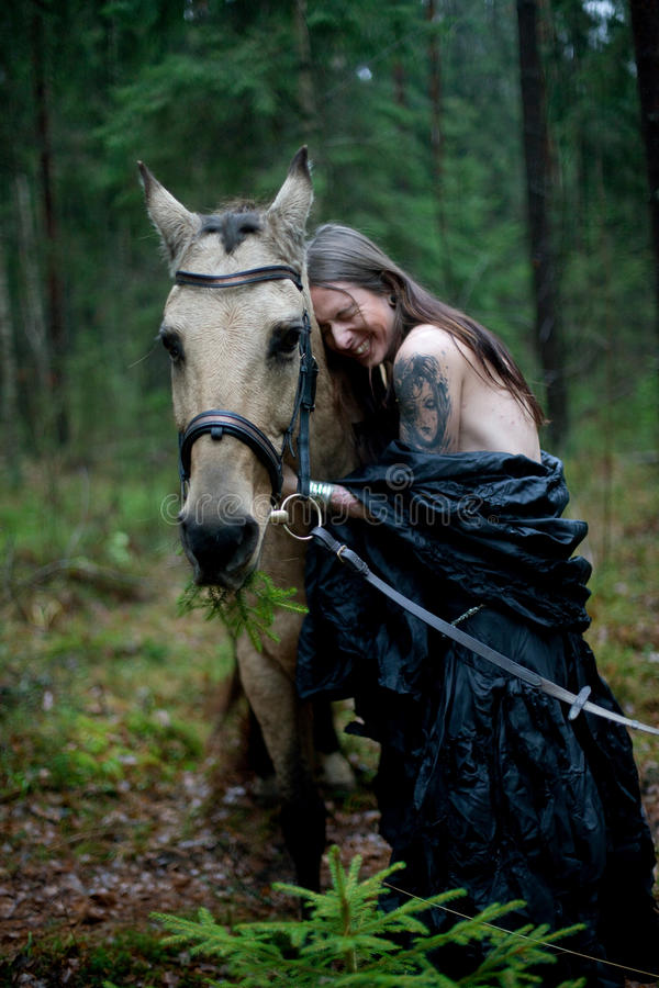 Young man with horse. Young man with long hair with horse in dark forest stock photography