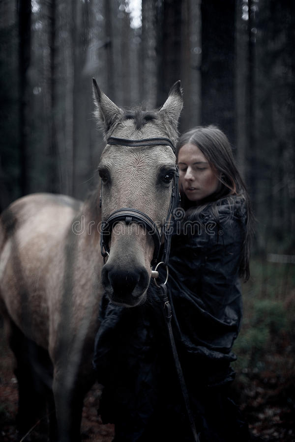 Young man with horse. Young man with long hair with horse in dark forest royalty free stock photos