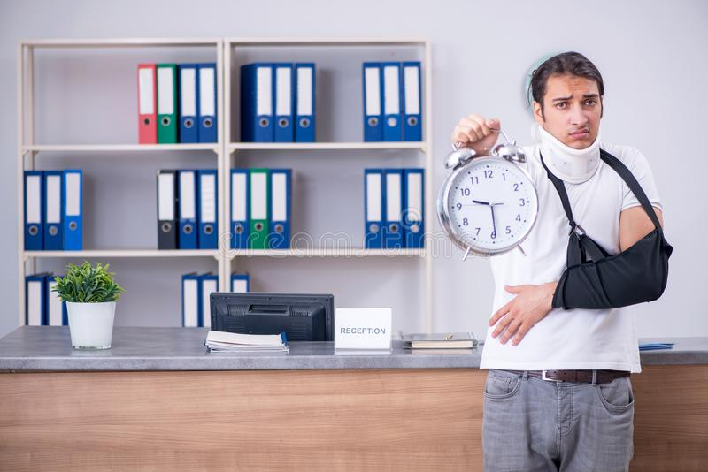 Young man at hospital reception desk royalty free stock images
