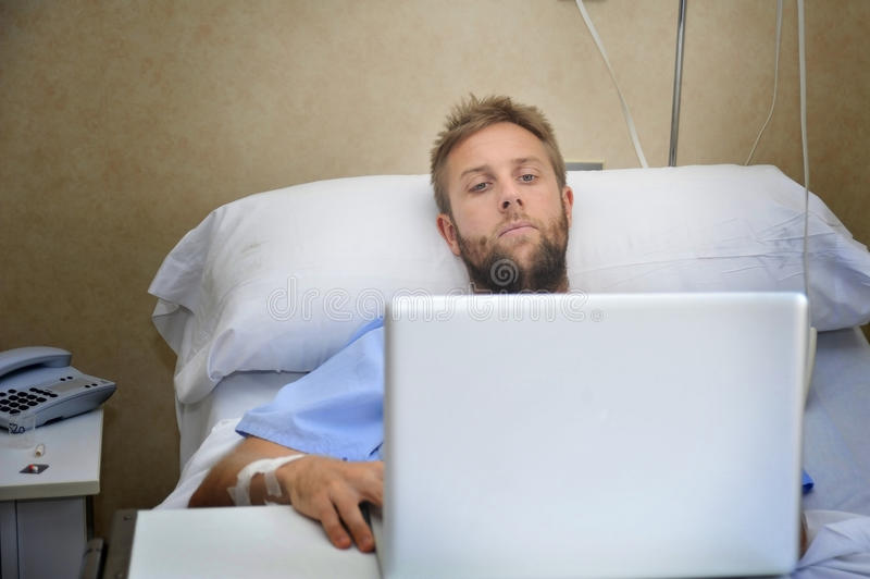 Young man in hospital room in bed using internet researching info on his own injury disease or sickness. Young man in hospital room lying in bed sick and injured stock photography