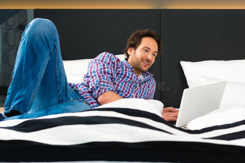 Download Young Man In Hotel In Bed With Wifi And Computer Stock Photo - Image: 33421128