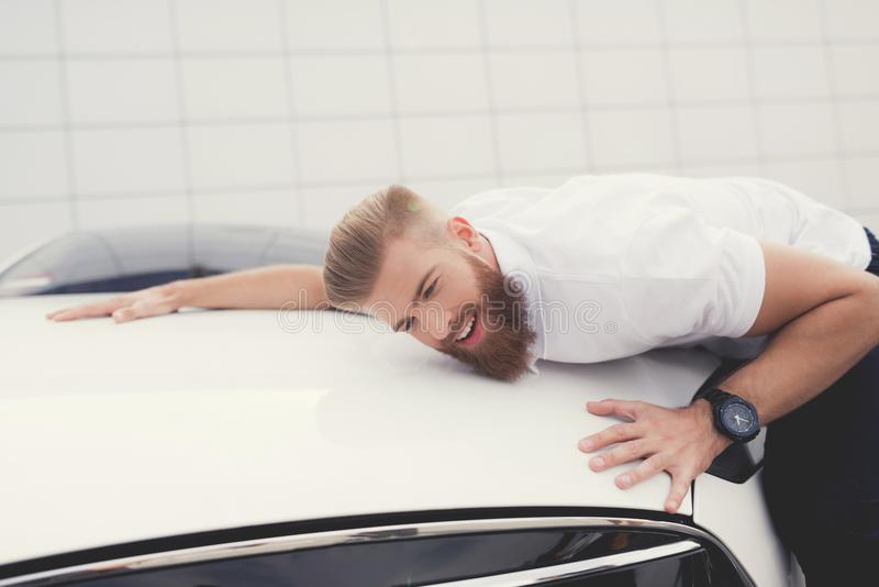 A young man is hugging his electric car. He is very glad that he has such a car. He smiles stock photo
