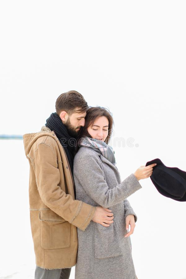 Young man hugging woman wearing grey coat and scarf in white winter background. Young men hugging women wearing grey coat and scarf in white winter background stock image