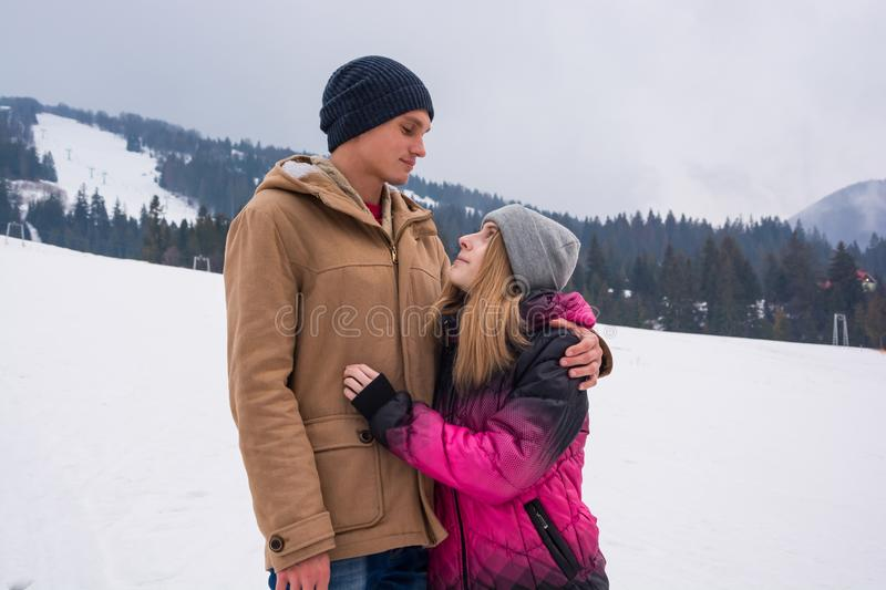 A young man hugs a girl and look at each other against a backdrop of a mountain landscape in winter royalty free stock image