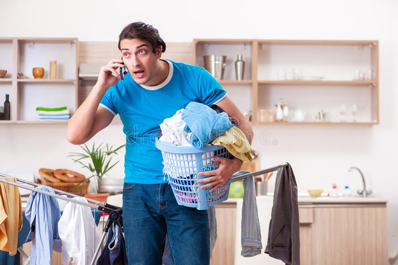 The young man husband doing clothing ironing at home. Young man husband doing clothing ironing at home stock photo