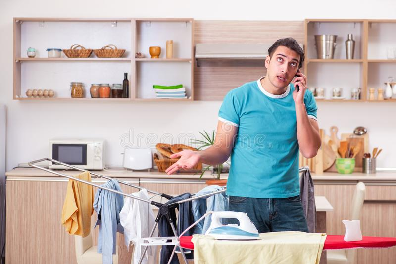 Young man husband doing clothing ironing at home. The young man husband doing clothing ironing at home royalty free stock photography