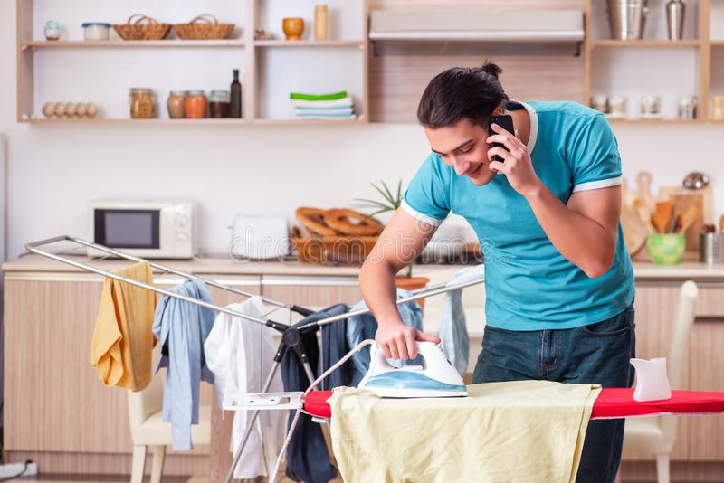 Young man husband doing clothing ironing at home. The young man husband doing clothing ironing at home stock photo
