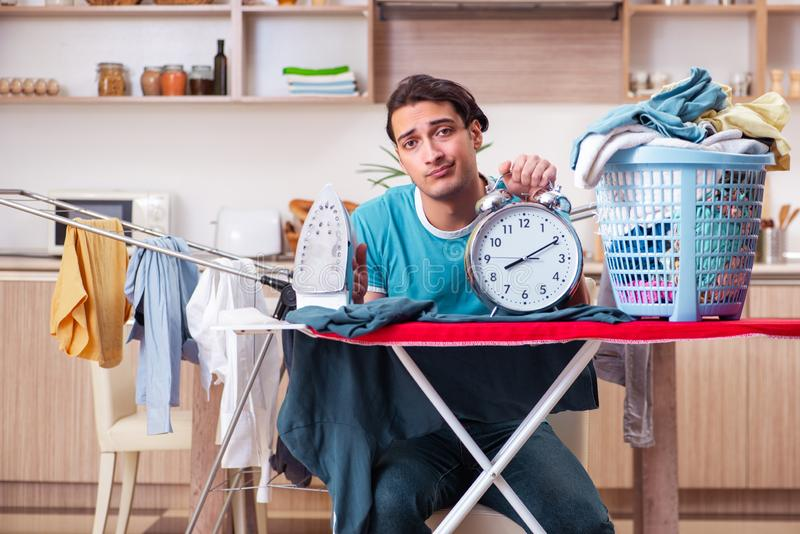 Young man husband doing clothing ironing at home. The young man husband doing clothing ironing at home royalty free stock images
