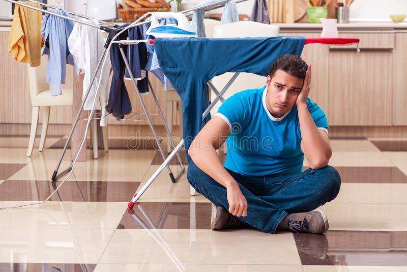 Young man husband doing clothing ironing at home. The young man husband doing clothing ironing at home royalty free stock photo