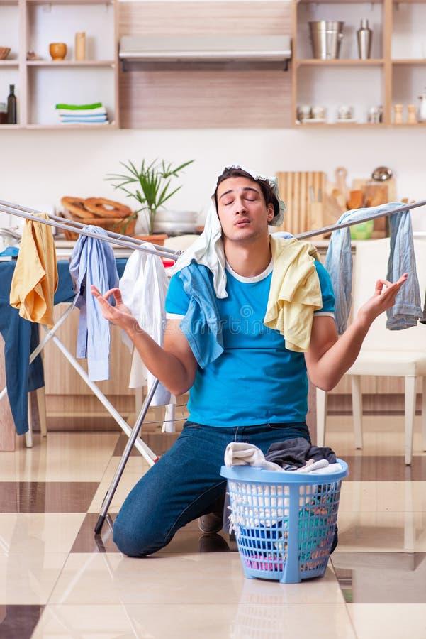 Young man husband doing clothing ironing at home. The young man husband doing clothing ironing at home stock photos
