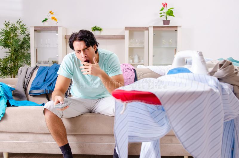 The young man husband ironing at home. Young man husband ironing at home royalty free stock photos