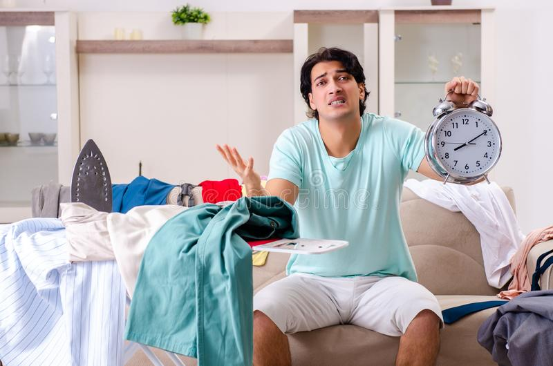 The young man husband ironing at home. Young man husband ironing at home royalty free stock images