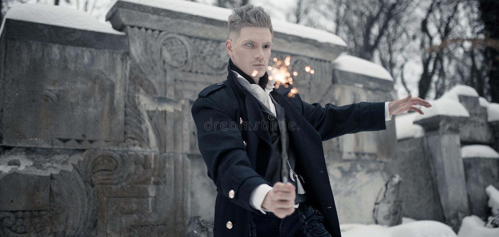 Young man in image of black magician makes a spell using magic wand royalty free stock images