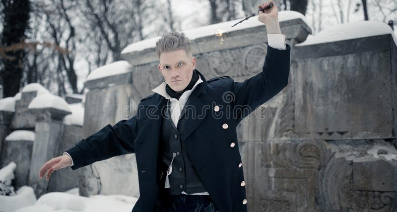 Young man in image of black magician makes a spell using magic wand royalty free stock image