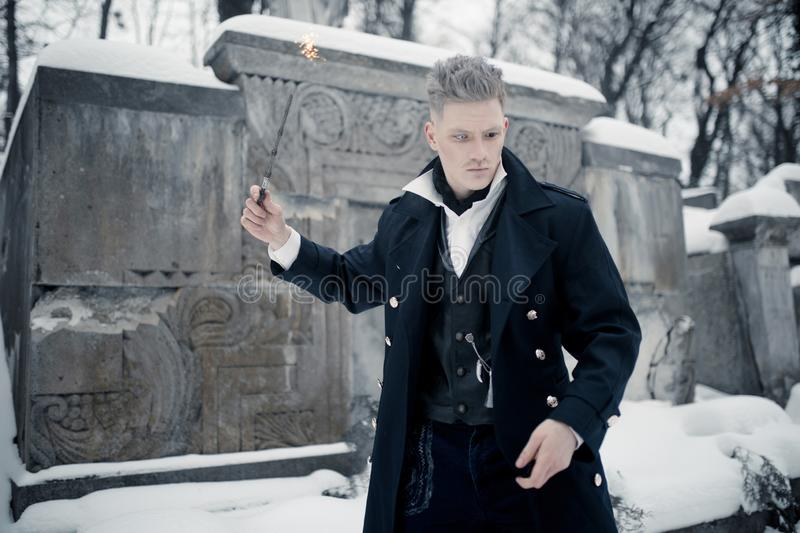 Young man in image of black magician makes a spell using magic wand stock image