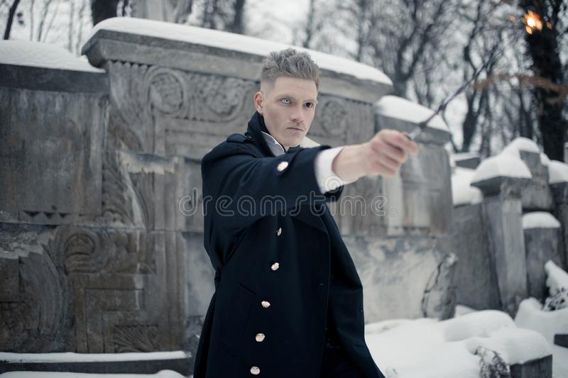 Young man in image of black magician makes a spell using magic wand royalty free stock photography