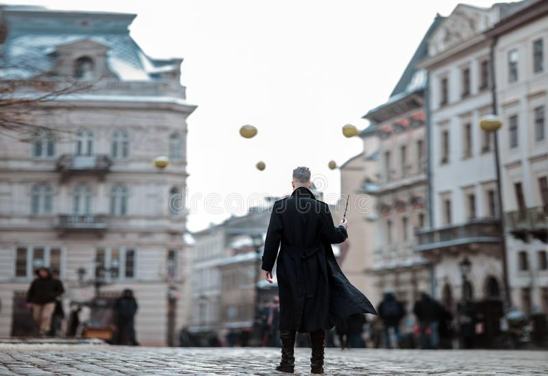 Young man in image of black magician walks on street with magic wand. Young man in image of black magician walks on city street with magic wand in his hand stock image
