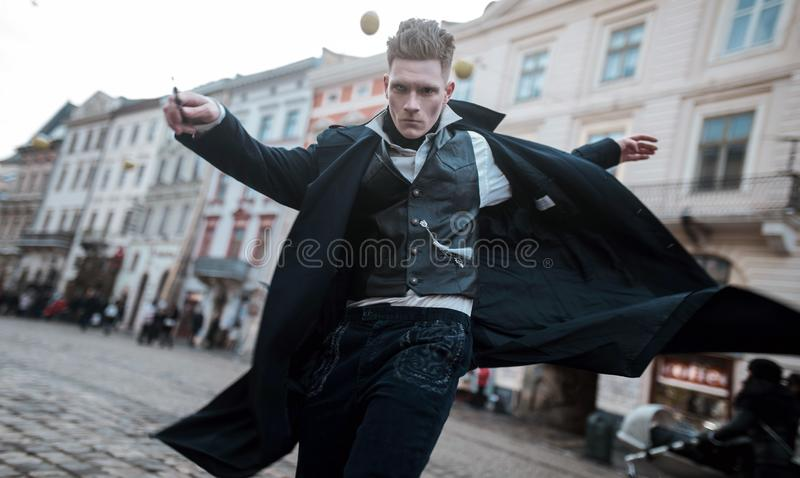 Young man in image of black magician walks on street with magic wand stock images