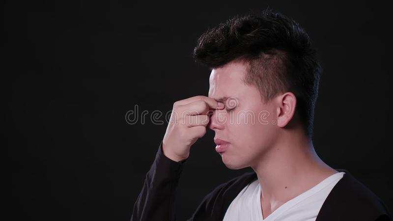 A Man Immitating Headache Against a Black Background stock images