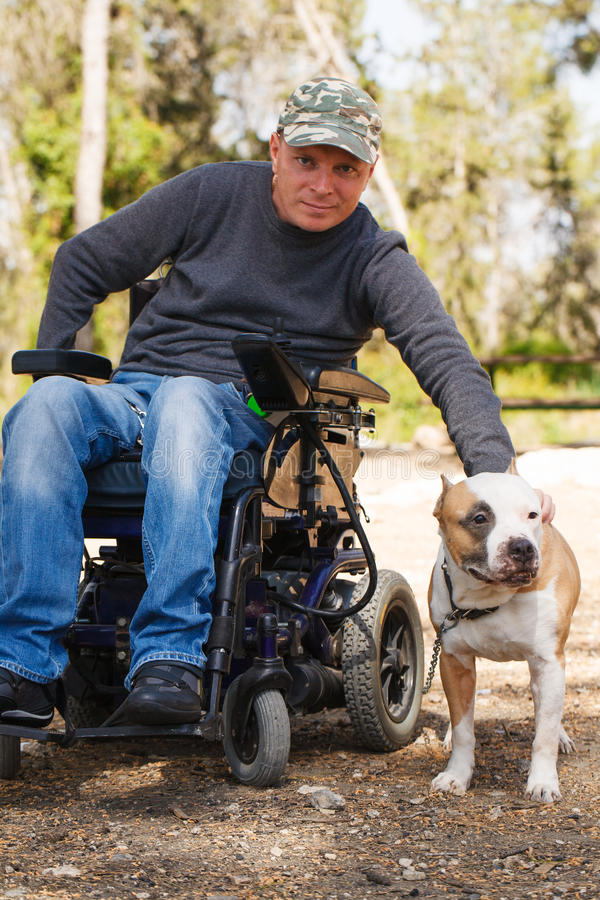Free Young Man In A Wheelchair With His Faithful Dog. Stock Photography - 29816662