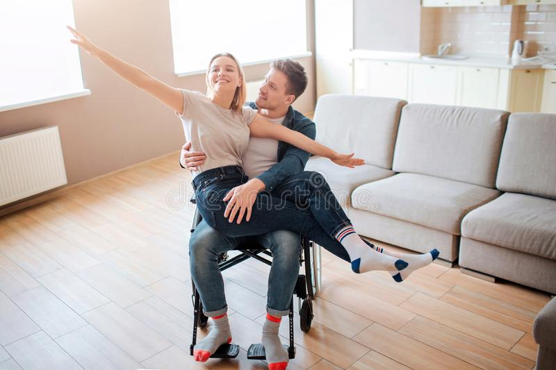Young man with inclusiveness holding girlfirend on knees. She is happy and full of joy. They smile. Person with special stock photos