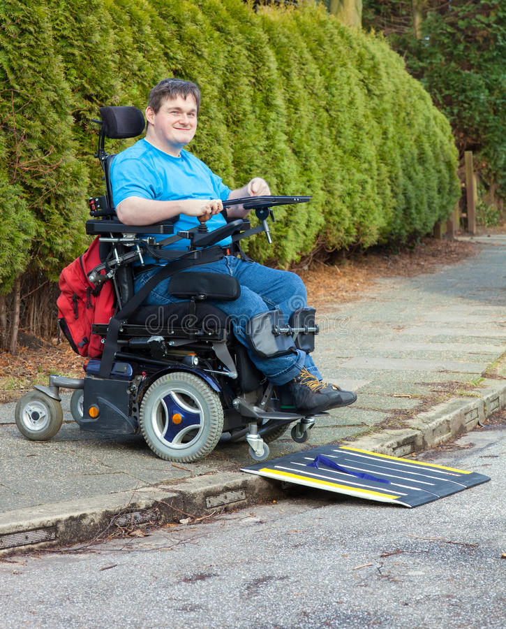 Young man with infantile cerebral palsy. Young man with infantile cerebral palsy caused by birth complications negotiating a mobile ramp on a roadside kerb with royalty free stock photo