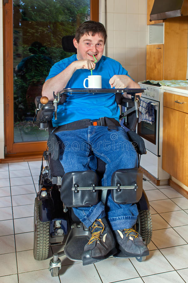 Young man with infantile cerebral palsy. Spastic young man with infantile cerebral palsy caused by complications at birth sitting in a multifunctional royalty free stock photo