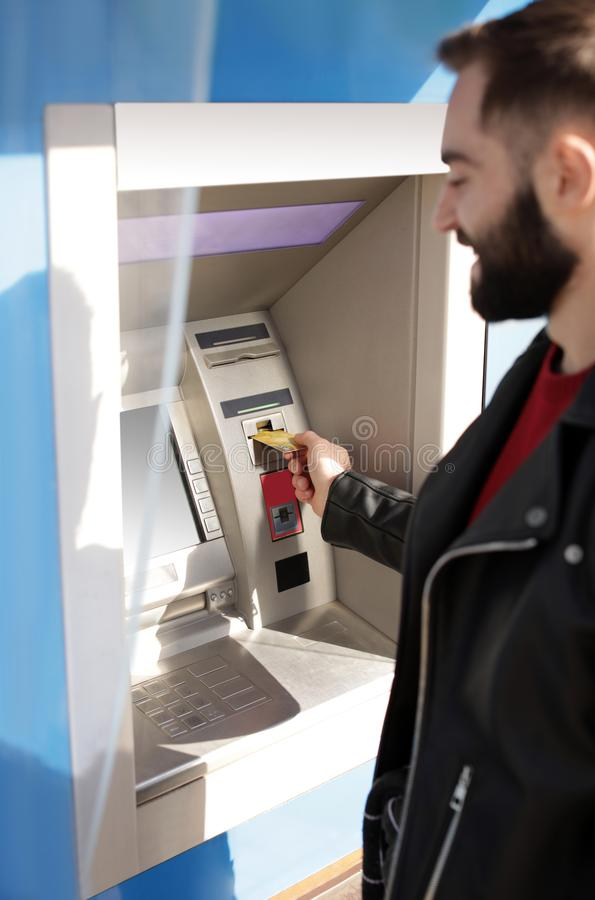 Young man inserting credit card into cash machine. Outdoors royalty free stock photos