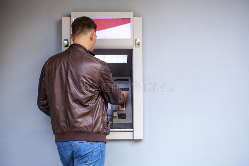 Young man inserting a credit card to ATM stock image