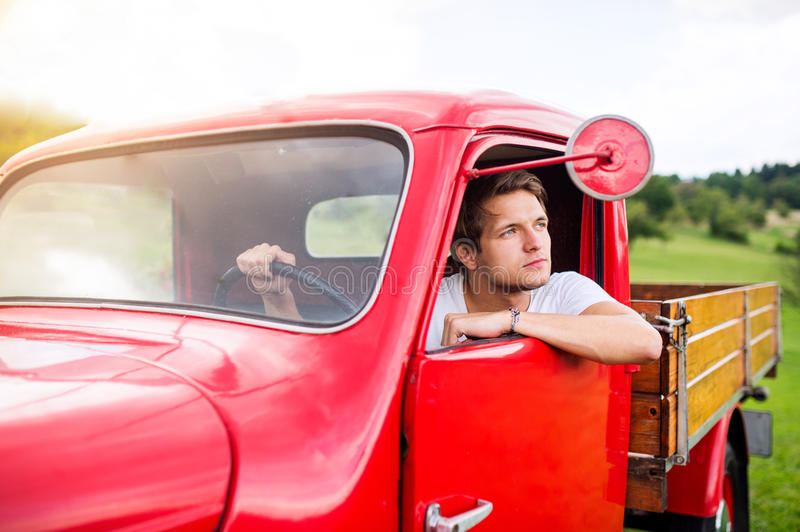 Young man inside red vintage pickup truck, green nature stock photo