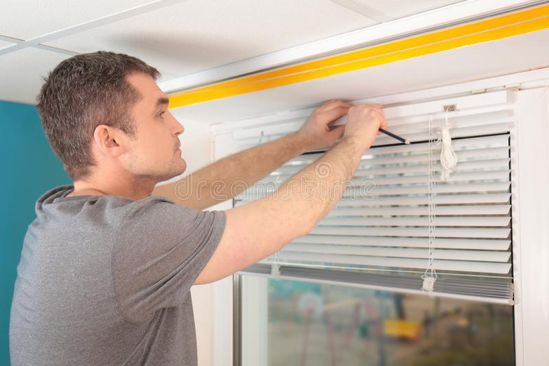 Young man installing window shades royalty free stock images