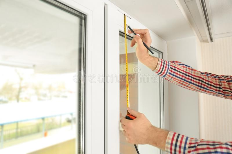 Young man installing window shades royalty free stock photography