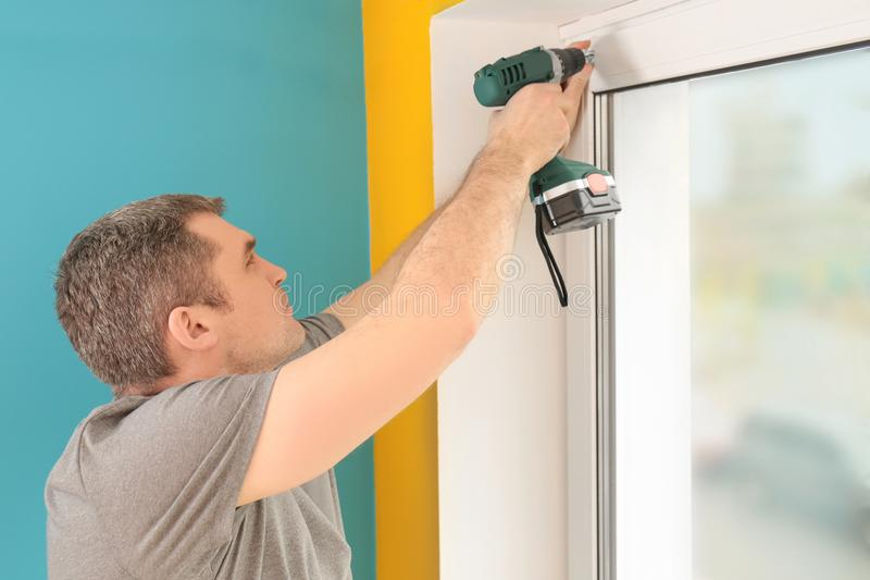 Young man installing window shades royalty free stock photo