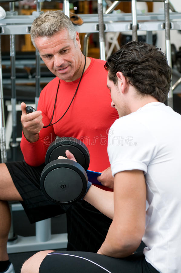 Young man with instructor at gym. Mature instructor checking and supervising fitness training at gym royalty free stock photo