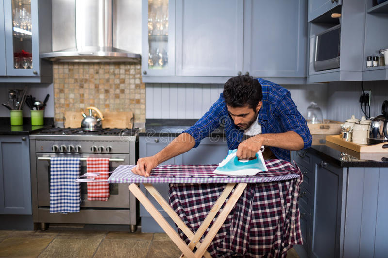 Young man ironing shirt on board. In kitchen at home royalty free stock photos