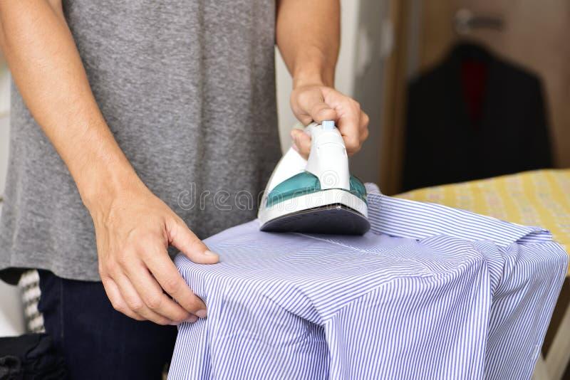 Young man ironing a shirt. Closeup of a young man ironing a striped shirt with an electric iron royalty free stock photos
