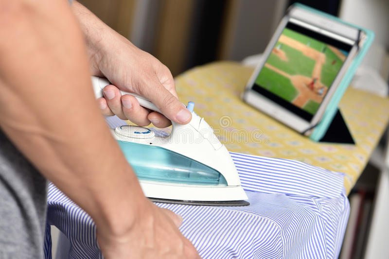 Young man ironing a shirt while watching sports online. Closeup of a young man ironing a striped shirt with an electric iron on an ironing board, while watches a stock images
