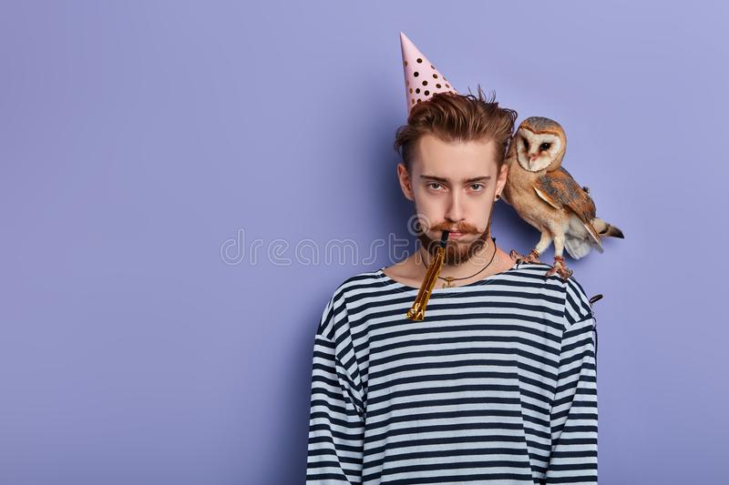 Young man isn`t satisfied with his birthday party. Frustration concept. isolated blue background, studio shot,copy space royalty free stock photos