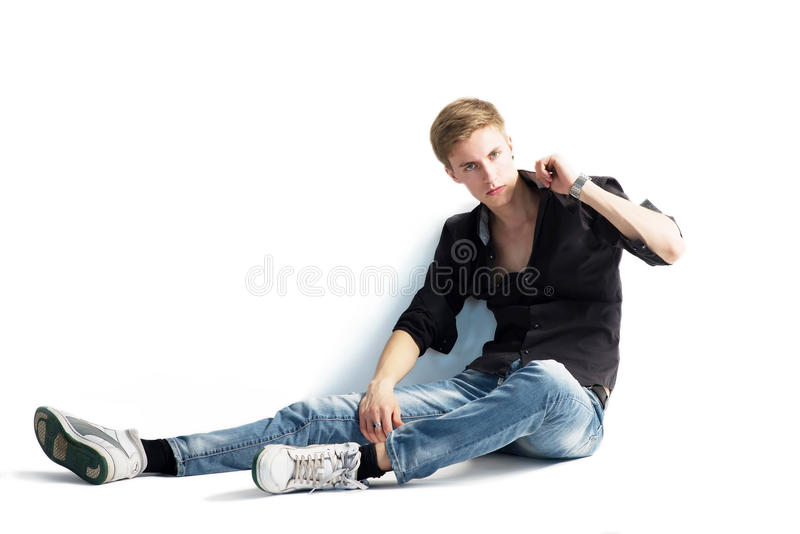 Young man isolated on white background. Sitting royalty free stock photos