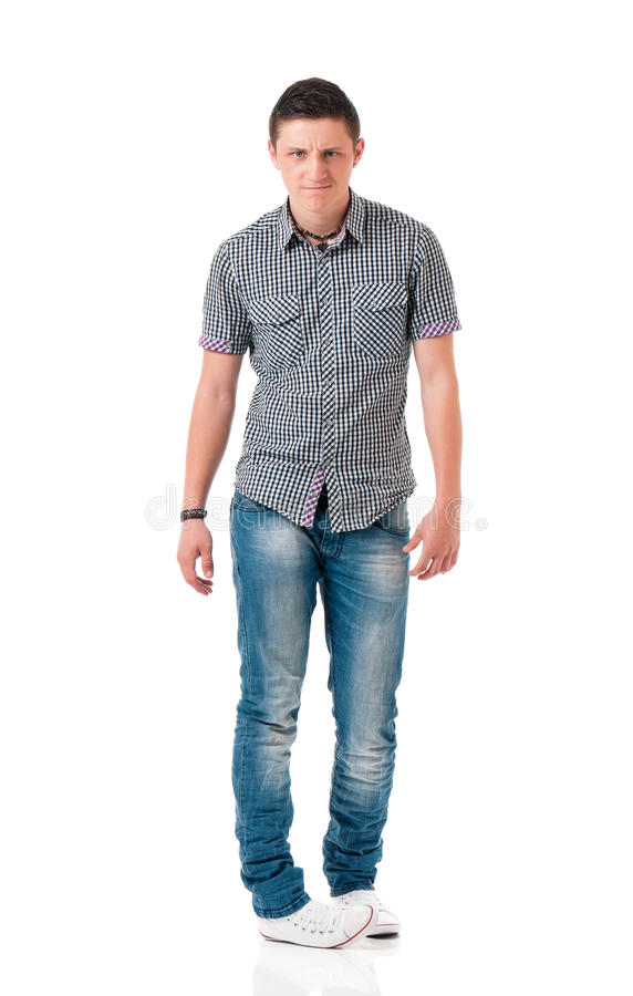Young man isolated on white. Serious suspicious young man standing, isolated white background. Full length portrait of anger teen boy stock photo