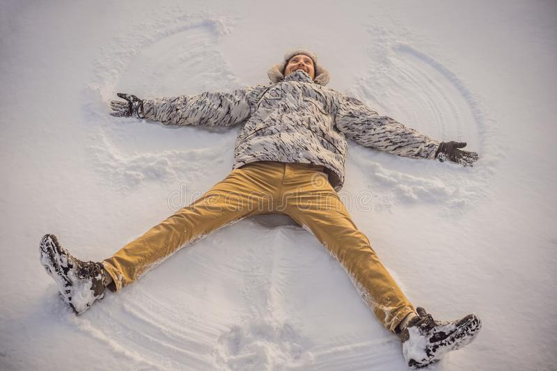 A young man in jacket lies on the snow and makes the figure of an angel. Winter fun stock photography