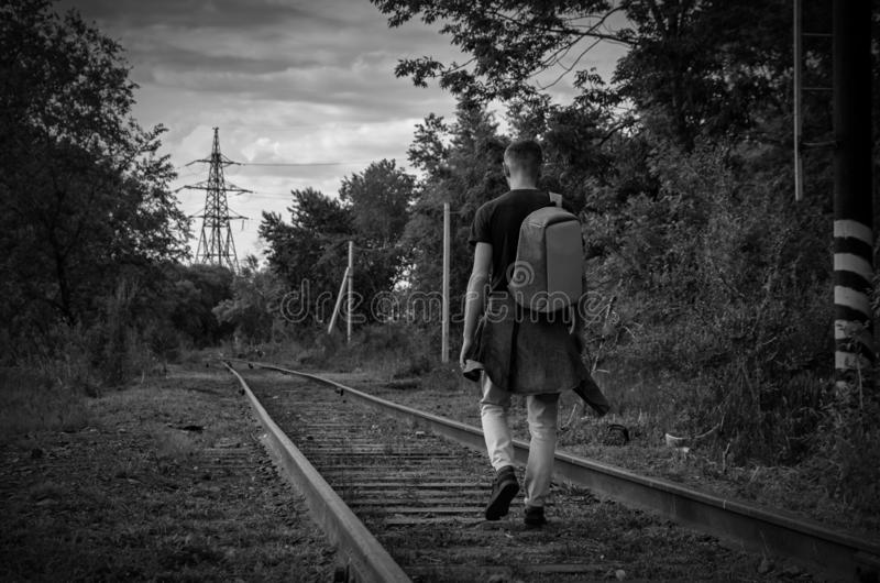 Young man in jeans with backpack on his back goes forward along abandoned railway. concept of frightening thing.  stock images
