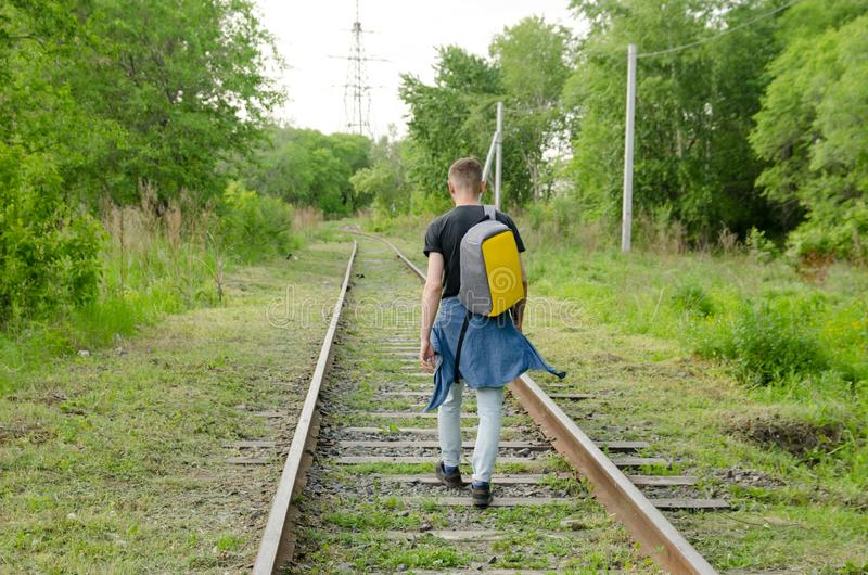 Young man in jeans with backpack on his back goes forward along abandoned railway. concept of traveling alone.  stock photos