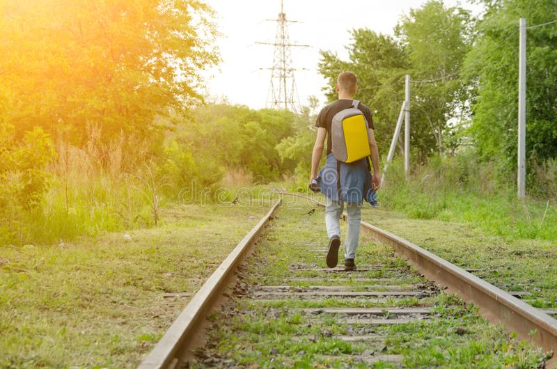 Young man in jeans with backpack on his back goes forward along abandoned railway in summer sunset. concept of walking travel.  stock photography