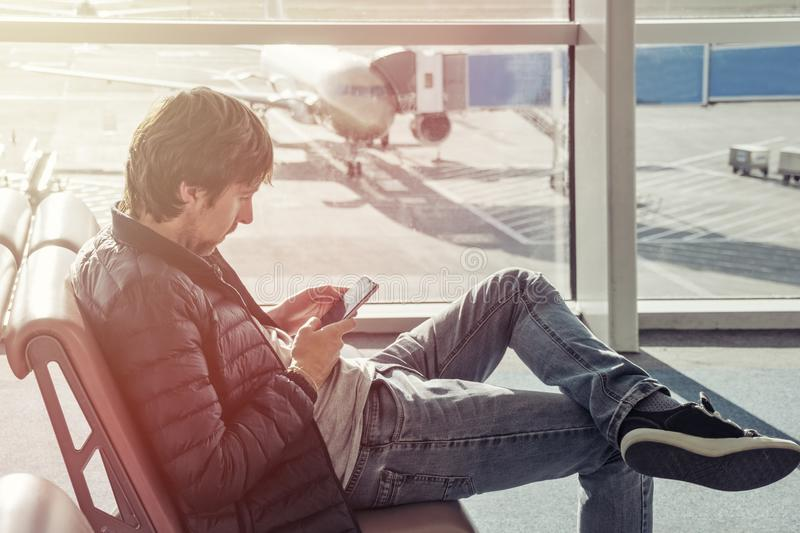 Young man in jeans and jacket sits on chair spend time by using mobile phone in airport lounge. Booking hotel in foreign country. royalty free stock image