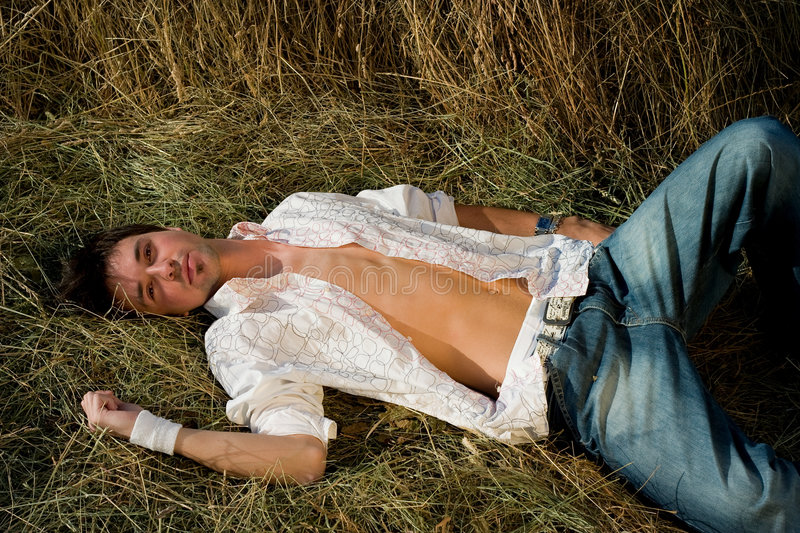 Young Man in jeans relaxing on the hay royalty free stock image