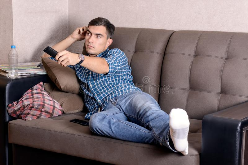 A young man in jeans, with a remote control for the TV boredom on the face changes the channel stock images