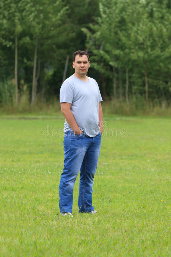Young man in jeans stands on green grass stock photography